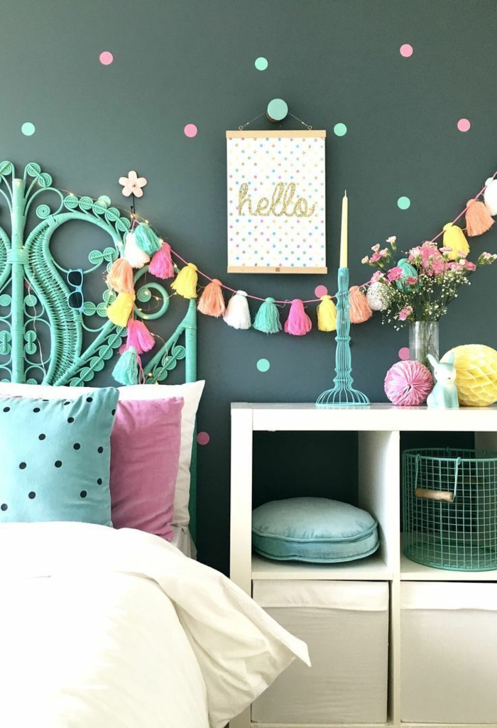 deco de chambre fille ado, ikea chambre fille, tete de lit en couleur réséda, mur en vert aux petits pois roses et verts, guirlande avec des pompons multicolores au-dessus du lit , coussin vert et rose sur la couverture lit en couleur ivoire