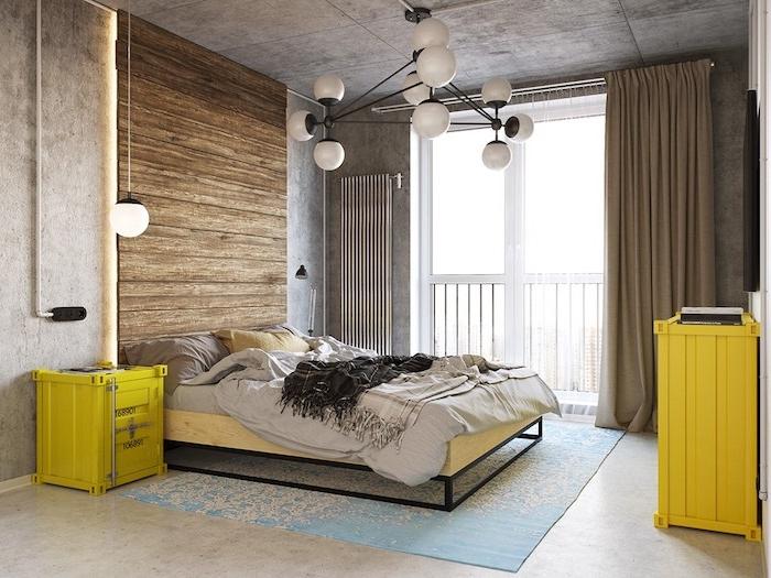 quel meuble industriel, table de nuit et commode couleur jaune, tete de lit bois, linge de lit gris, tapis bleu, murs et plafond effet béton et suspensions boules