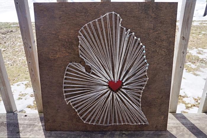 modèle de tableau en bois foncé avec création en fil blanc et petit coeur rouge au centre comme un objet DIY