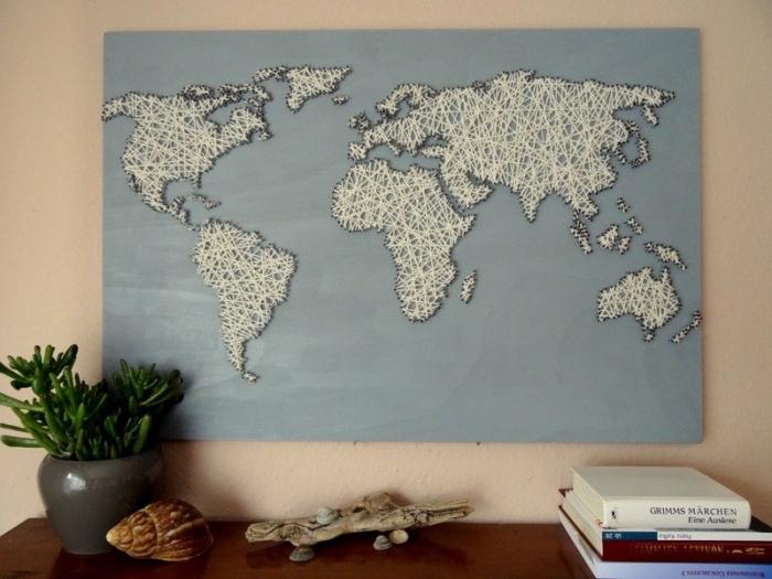 grand tableau de bois peint en bleu clair avec carte du monde en fil blanc et contours à fil noir comme un objet diy facile
