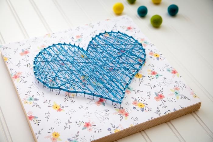 jolie création DIY sur une planche de bois de forme rectangulaire couverte de papier scrapbooking coloré et de fil bleu