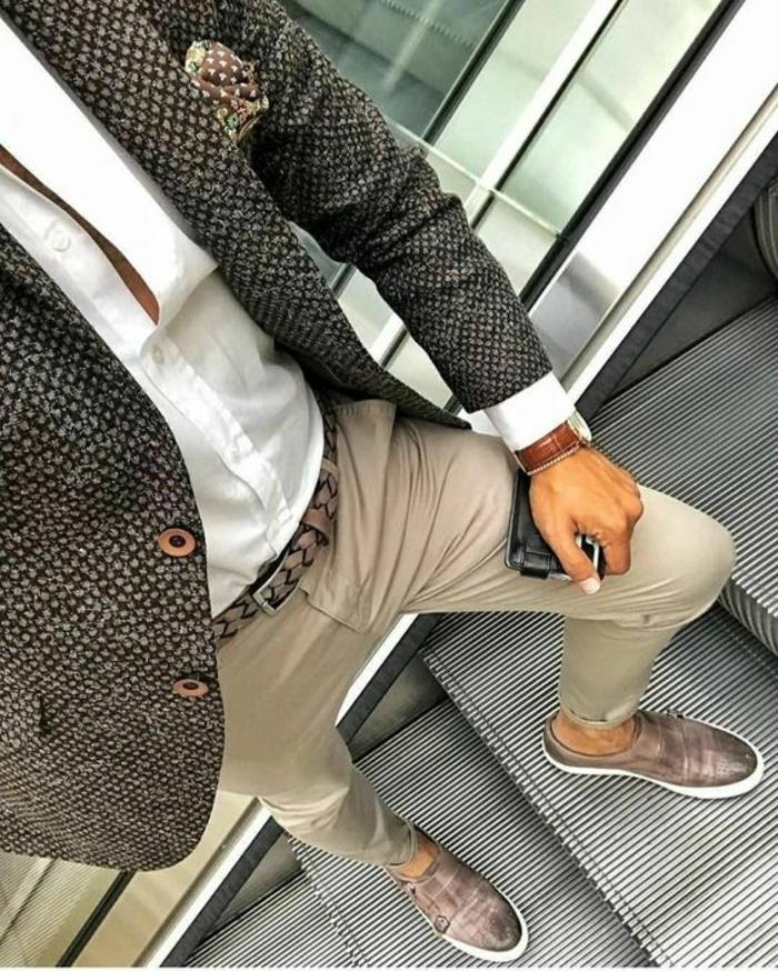 vetement homme stylé, pantalon couleur sable avec ceinture tressée en taupe, chaussures arrondies en taupe et semelle blanche, veste en laine fine en noir et beige, mouchoir de soie