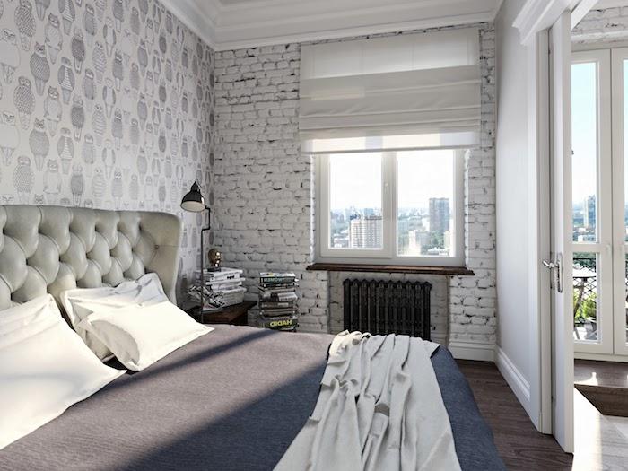 deco industrielle pas cher en papier peint imitation briques, linge de lit gris et blanc, tête de lit capitonnée, parquet marron foncé, pile de livres