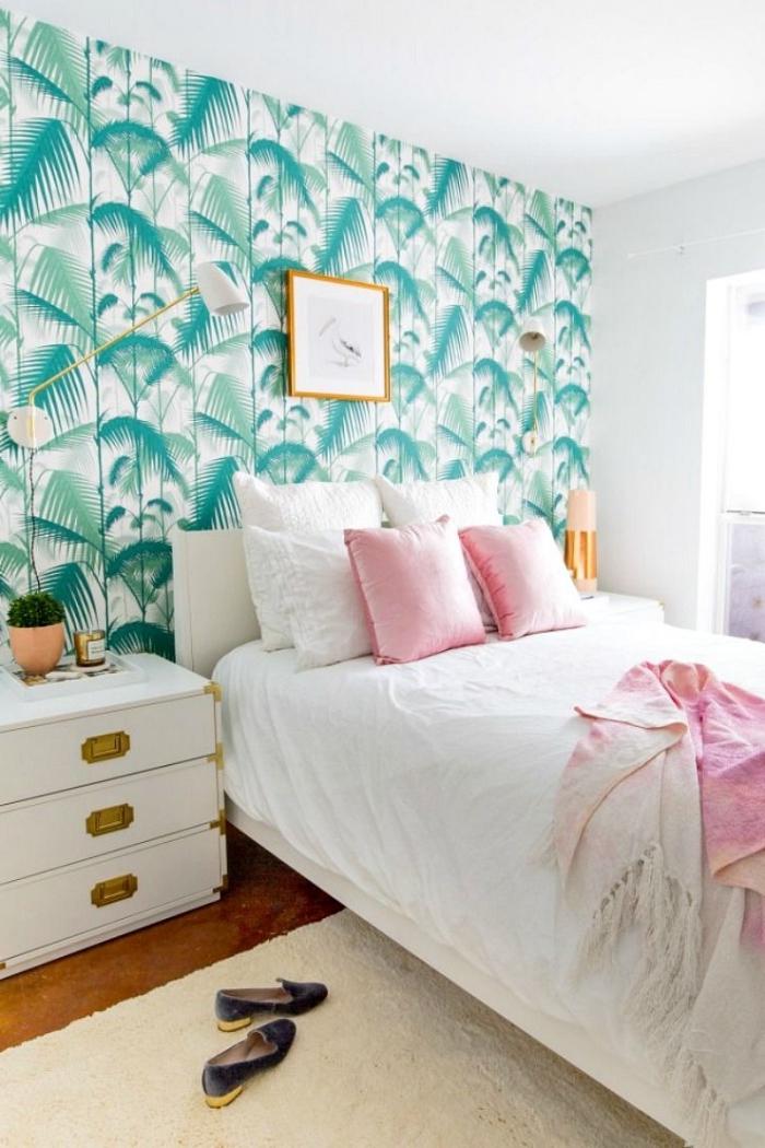 une chambre à coucher élégante et douce avec un espace lit délimité pair la tête de lit en papier peint à motif feuille de palmier
