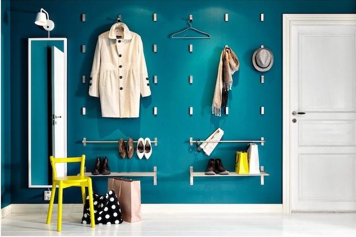 patere original en accroches metalliques installés sur un mur bleu canard, accents deco jaunes, rangement vetements et chaussures