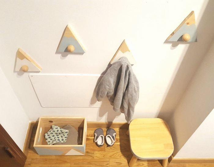 exemple e porte manteau scandinave en triangle de bois colorés imitation montagne sur un mur blanc, parquet clair
