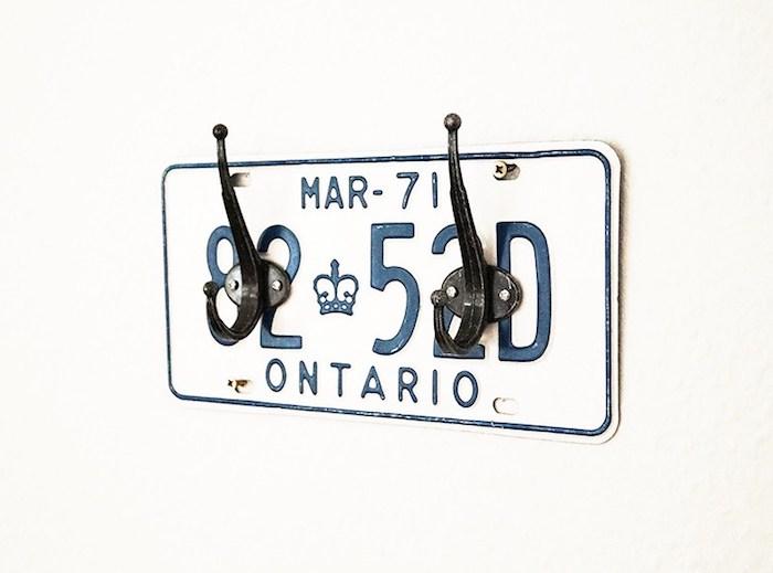 plaque d immatriculation couleur blanche avec des chiffres bleu foncé et des accroches metalliques noires