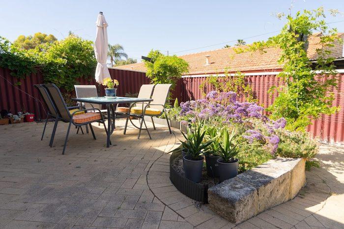 pavage exterieur, table et chaises métalliques, séparation jardin en panneaux de métal, plantes en bordure