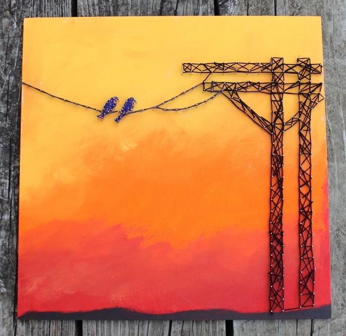objet fait main avec planche de bois et quelques couches de peinture orange et rouge à design coucher de soleil et oiseaux