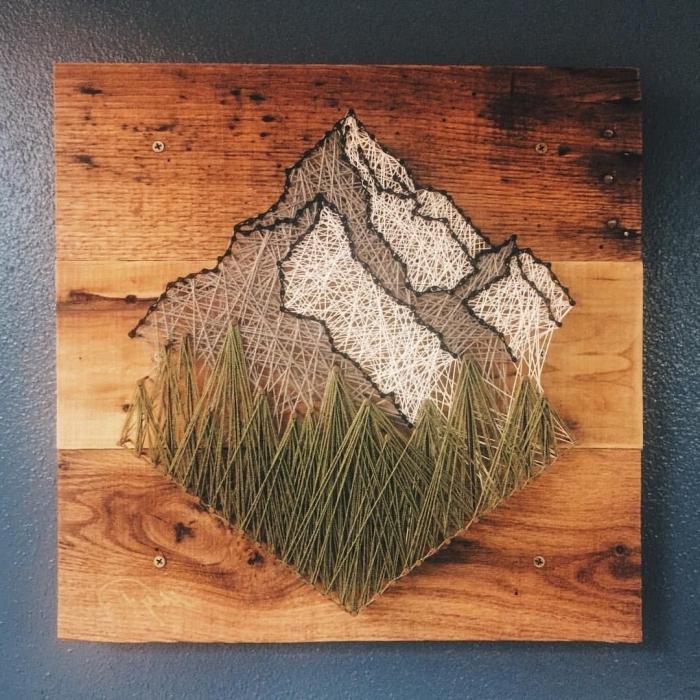 modèle de décoration murale fait main à partit de planche de bois foncé et fil en forme de paysage montagne