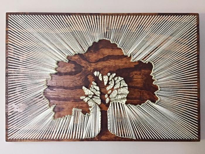 exemple de décoration murale DIY sur une planche de bois foncé à design arbre fabriqué avec fil et clous