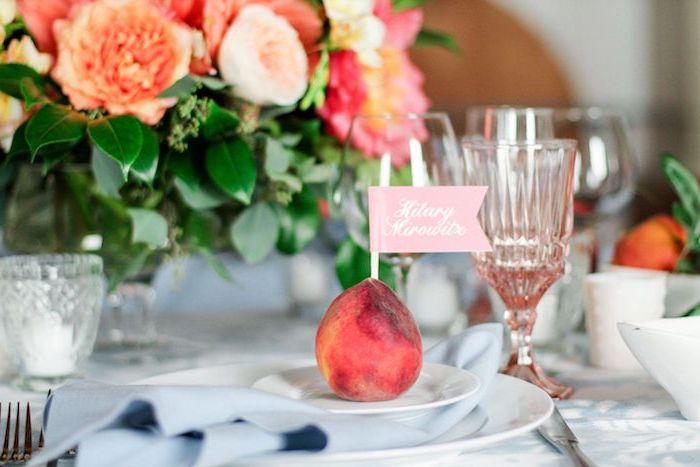 porte nom mariage en pêche avec une étiquette sur batonnet planté dedans, assiettes blanchs, centre de table mariage floral champetre chic