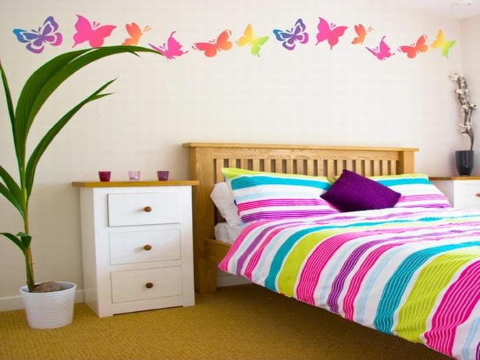 idée déco chambre, mur en couleur beige avec des motifs papillons en couleurs rayonnantes arc-en-ciel, meuble de chevet simple en blanc avec plan marron clair, tete de lit en bois marron clair, moquette couleur moutarde