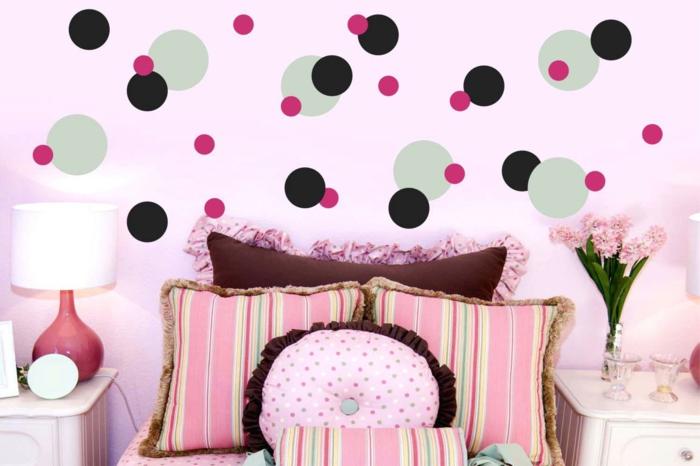 déco chambre ado fille, murs roses avec des pois vert réséda, rouges et noirs, gros coussins carrés et ronds au lieu de tete de lit, luminaire de commode avec abat-jour blanc