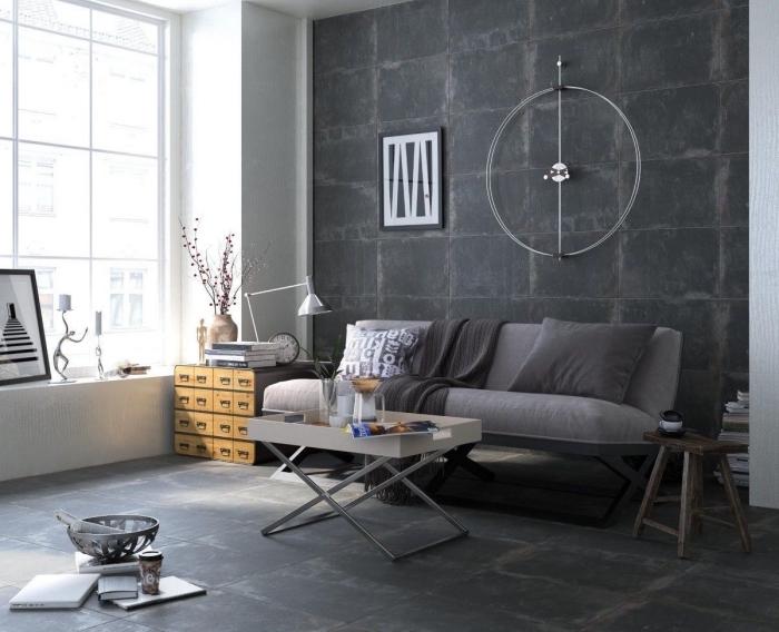 salon de style industriel avec mur gris foncé et grande fenêtre, canapé gris couvert de coussins et plaid décoratifs en nuances de gris