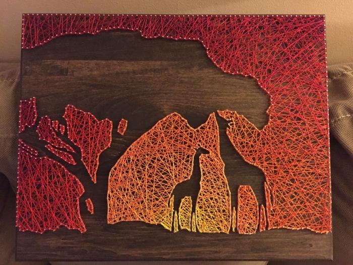 magnifique création sur le thème d'Afrique avec une planche de bois foncé et un paysage coucher de soleil et girafes en fil à coudre