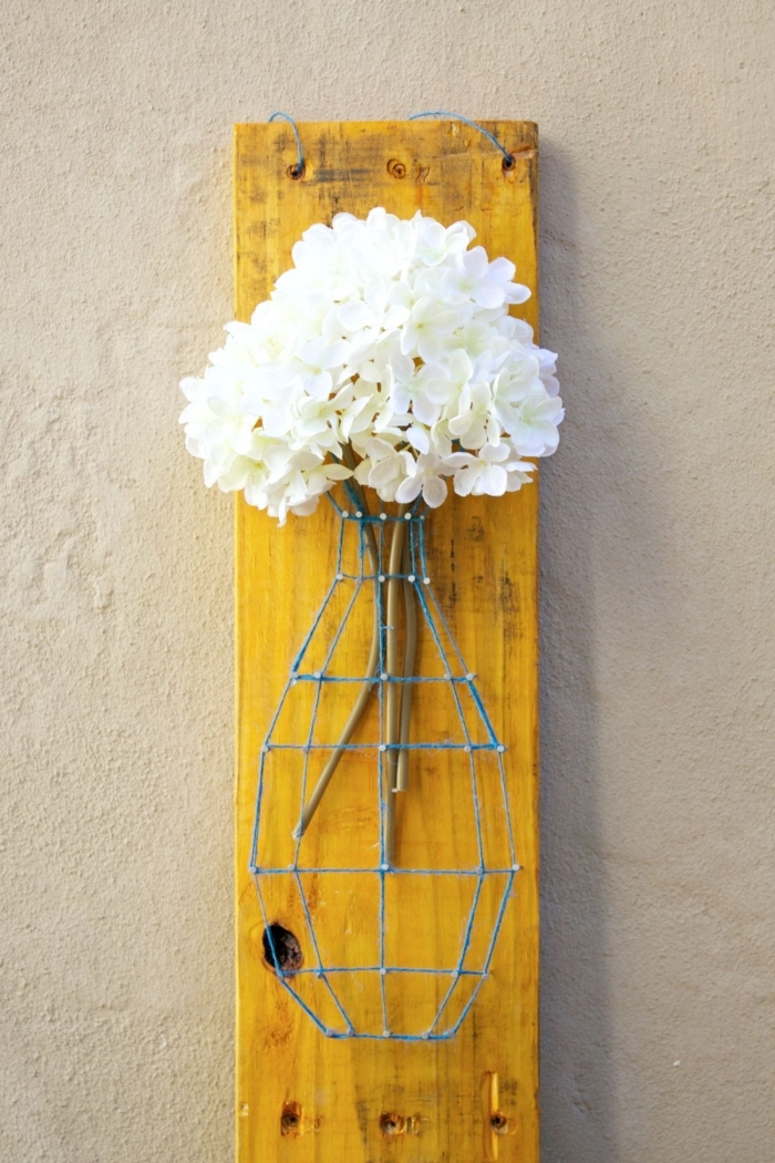 joli vase décorative en fil bleu et clous remplie de fleurs blanches sur une planche de bois peinte en jaune