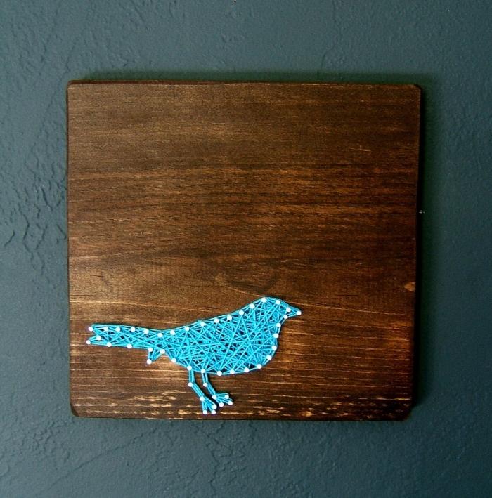 exemple de jolie décoration murale en panneau de bois foncé de forme carré avec mini oiseau en fil turquoise et clous blancs