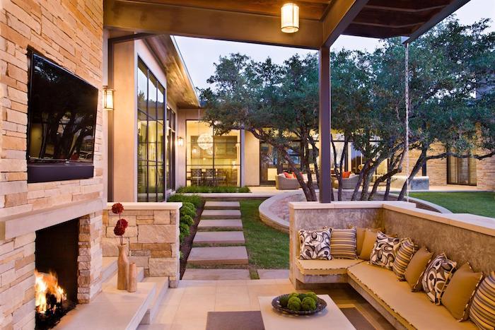 terrasse d exterieur abritée sous une pergola, canapé confortable décoré de coussins, cheminée en pierre, table basse