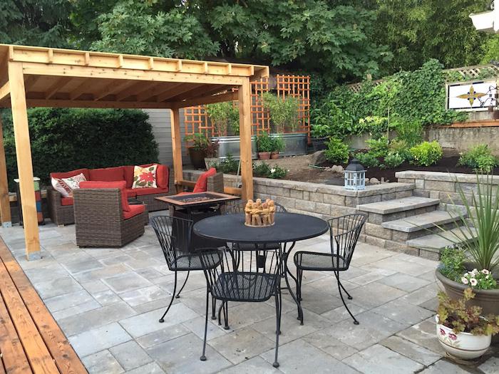 pergola bois qui abrite un salon de jardin en rotin avec canapé et fauteuils, table et chaise noires métalliques, revetement dalles de béton, coin jardin