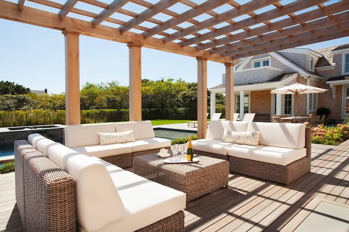 pergola bois adossée à une maison moderne, canapés et table tressés, revetement en bois composite