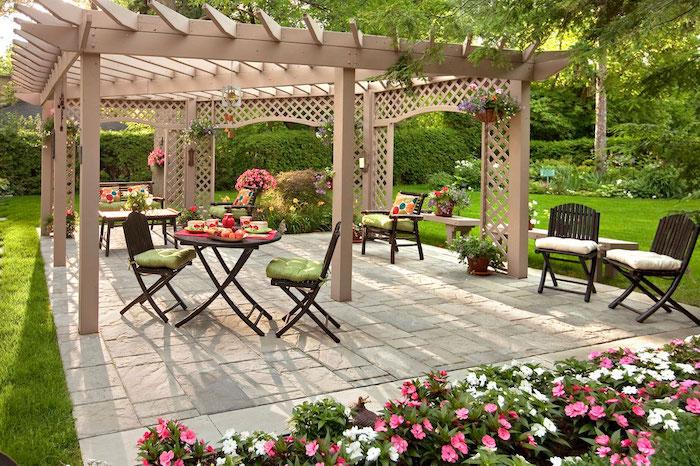 aménagement extérieur jardin terrasse avec des chaises et table bois, bordure de fleurs, gazon vert, pergola bois