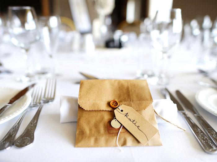 sachet papier kraft avec un petit cadeau invité et etiquette mariage porte nom, vaisselle et nappe blanche, couverts argent