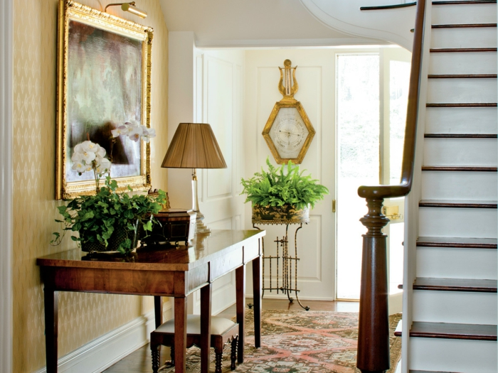 table en bois pour le hall d'entrée, lampe à abat-jour, peinture au cadre doré, tapis vintage, plantes vertes