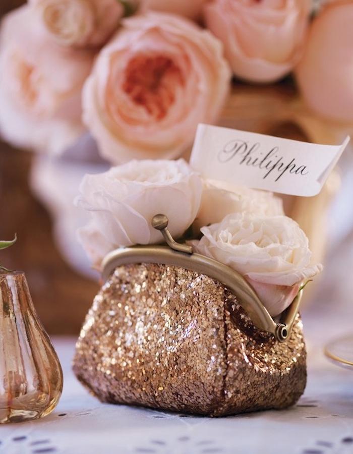 porte monnaie pailleté avec des roses blanches à l intérieur, étiquette nom invité blanc et centre de table pivoines