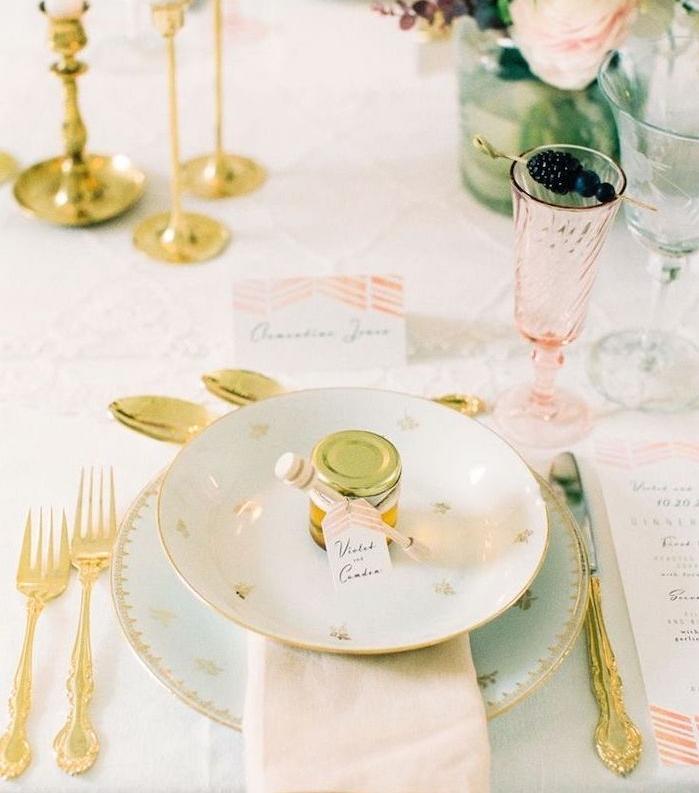 petit pot de miel dans assiettes, couverts dorés et centre de table floral, nappe blanche, verre rose transparente