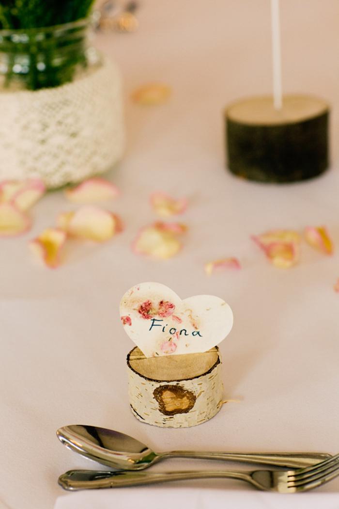 petite rondelle de bois avec une incise et coeur en papier prénom mariage, pétales de fleurs, centre de table floral