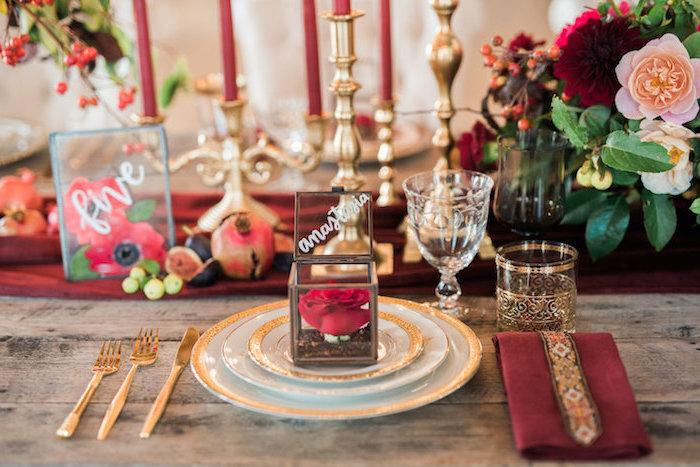 petit terrarium en cube de de verre avec terreau et rose rouge, chemin de table rouge, bouquets de plantes et bougeoir doré, table bois brut