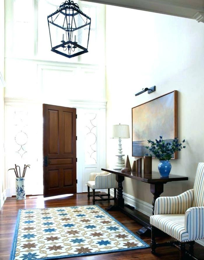 entrée dans une maison blanche, console en bois foncé, deux fauteuils rayés, luminaire lanterne et grande peinture