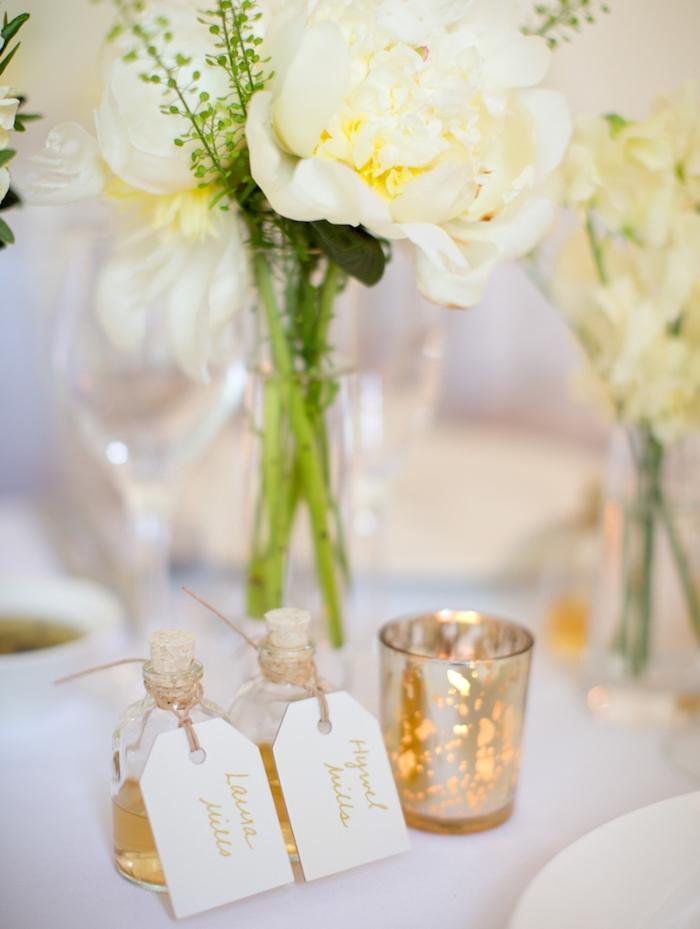 petites fioles remplies de boisson avec carton nom invité, centre de table en bouquets de fleurs dans un vase, bougeoirs diy