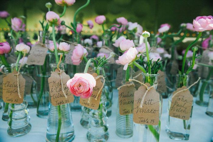idée de petit soliflore en bouteille de verre avec une fleur dedans et carton papier kraft, numéro de table et nom invité