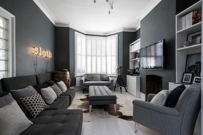 ambiance cozy dans un salon au plafond blanc et murs foncés avec meubles moderne, modèle de canapé gris foncé couvert de coussins