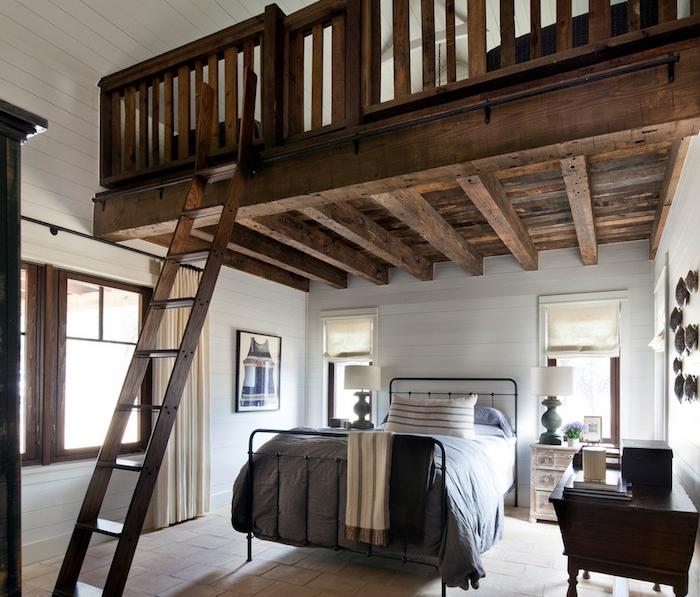 lit métallique noir avec linge de lit gris, sol en carrelage grès cérame, mezzanine en bois avec échelle, lambris blanc
