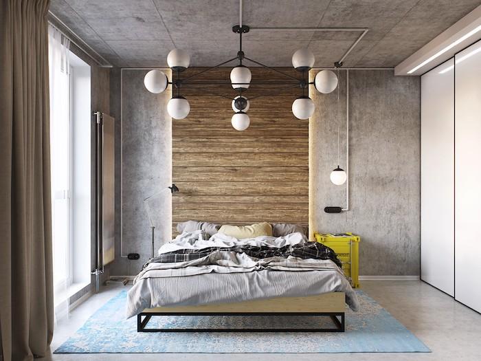 murs gris anthracite, linge de lit gris et beige, tapis bleu, armoire blanche, rideaux gris, sol gris clair, suspensions blanches originales