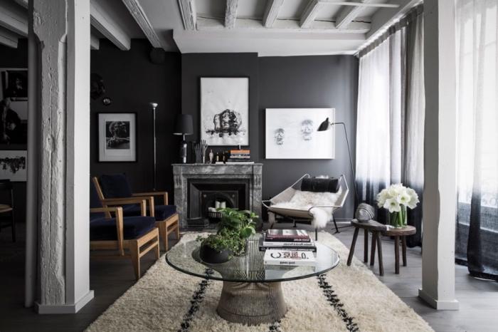 ambiance chaleureuse dans un salon au plafond blanc avec poutres et colonnes décoratives blanches combinées avec murs en gris anthracite