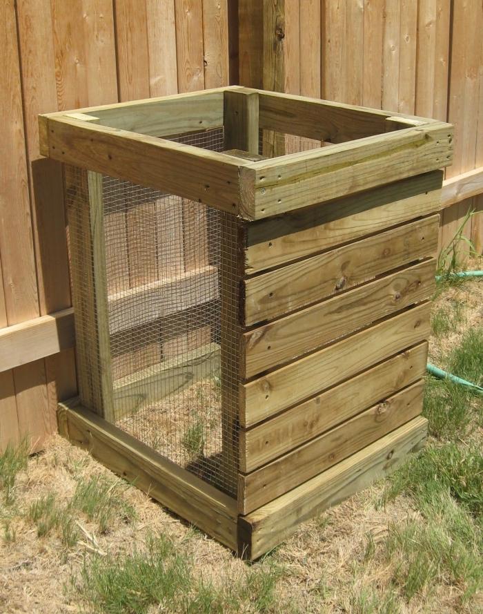 modèle de petit composteur de jardin fabriqué de planches de bois et grillage carré installé dans un coin de jardin