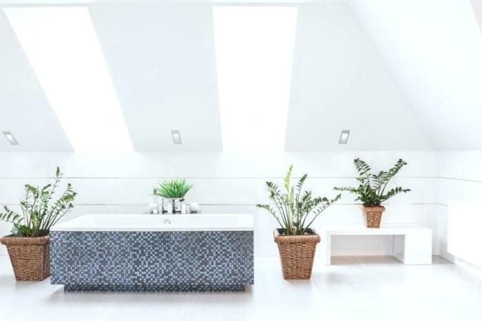 baignoire rectangulaire blanche revêtue de carrelage mosaïque en bleu et gris, plafond avec deux fenêtres rectangulaires, espace lumineux, plante salle de bain, 4 grands pots de plantes vertes