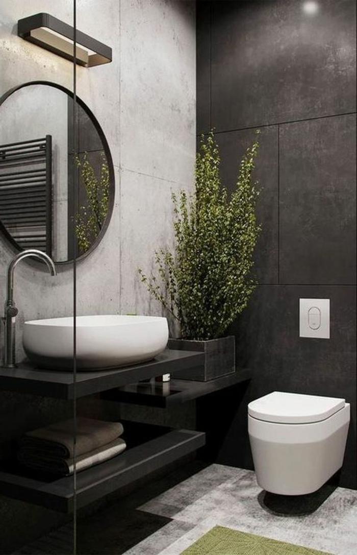 salle de bain en noir, blanc et gris, grand miroir rond au cadre fin en noir, plante interieur ombre, meuble wc suspendu blanc au design moderne