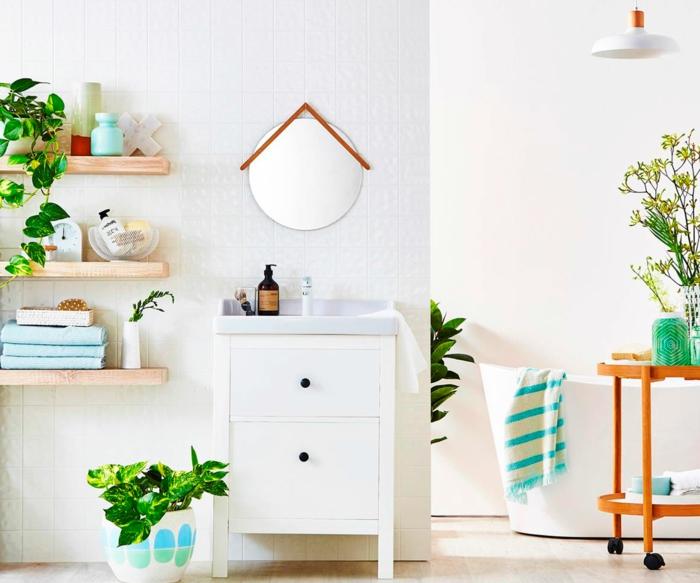 salle de bain verte, étagères en bois pvc clair, meuble blanc avec des poignées noires, miroir suspendu, murs en blanc, grande baignoire ovale blanche