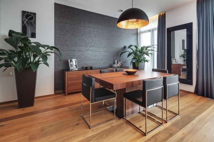 ambiance moderne et accueillante dans une salle à manger avec meubles de bois et décoration murale en peinture gris foncé