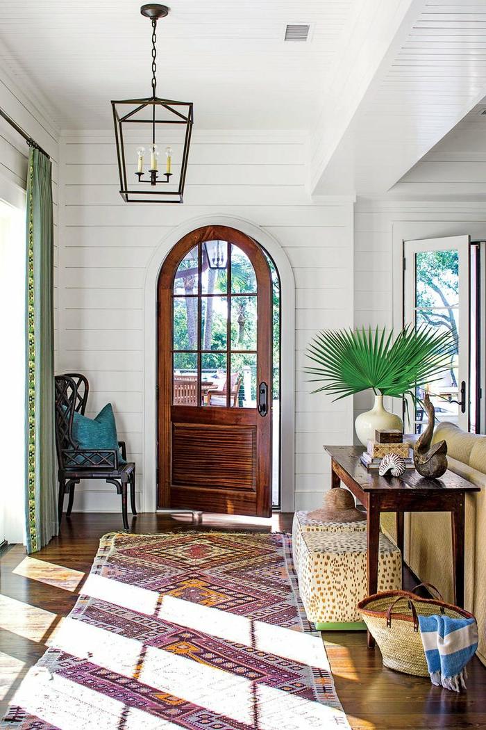 mur blanc et porte arquée, lanterne suspendue, petite table en bois foncé
