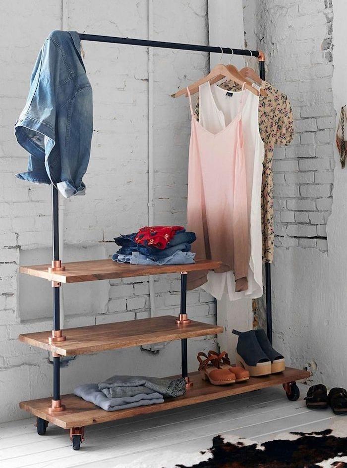 dressing porte manteau design sur pied en planches de bois comme rangement chaussures et poteau metallique pour suspendre vetements sur de cintres, parquet blanchi, mur de briques blanches defraichi