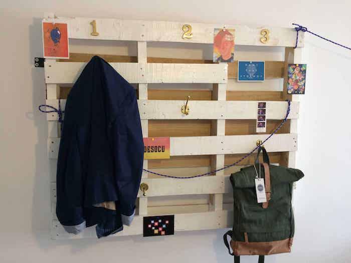 porte manteau mural en bois de palette avec des accroches dorées pour suspendre manteaux et autres vetements et accessoires