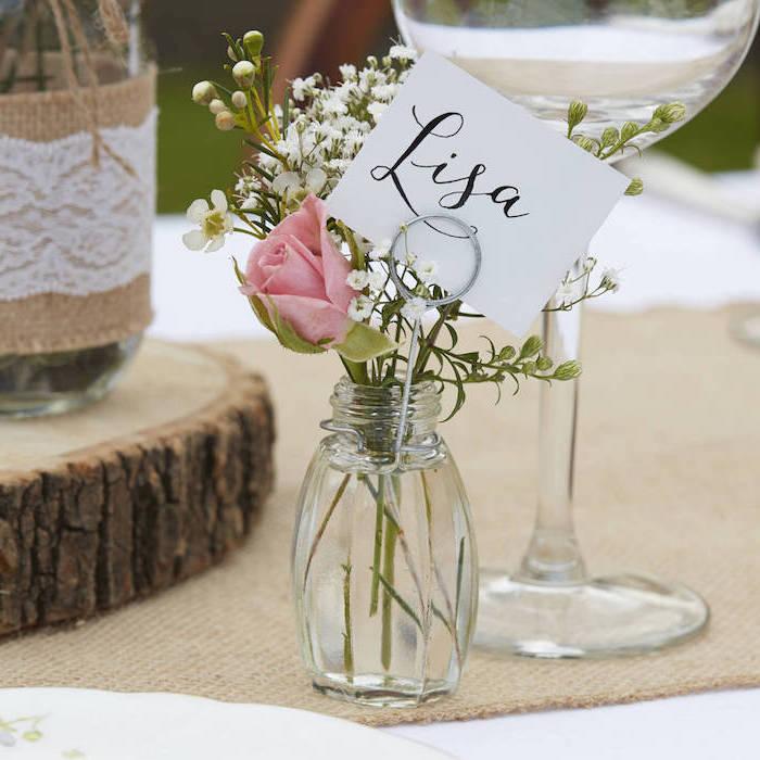 dentre de table mariage en rondin de bois et pot en verre vase décoré de toile de jute et dentelle, vase en salière avec petit bouquet de fleurs champetre etiquette pénom invité