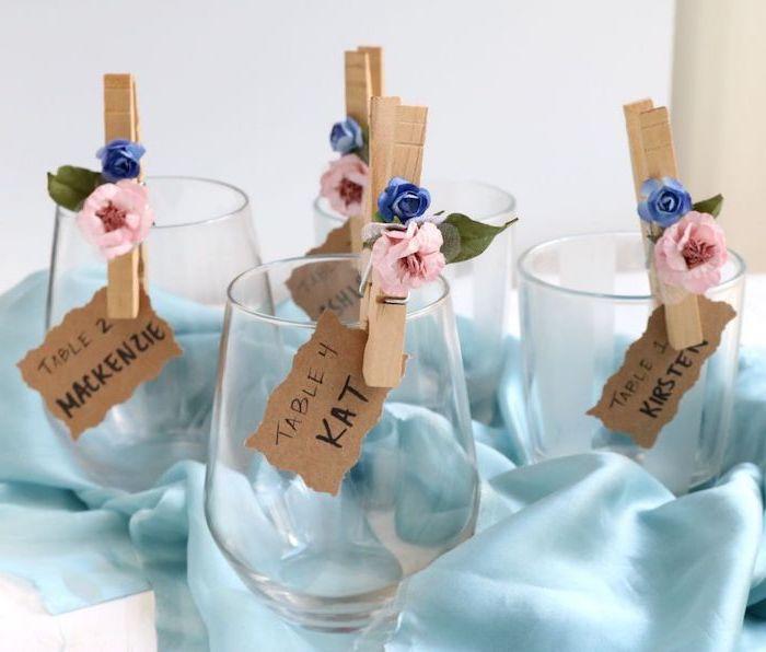 porte nom en pince à linge bois décoré de petites fleurs artificielles, toile de soie bleue, nappe blanche