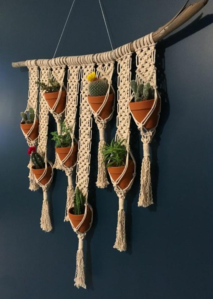 habiller un mur avec un porte-plante en macramé beige, plantes vertes exotiques, cactus, suspendus dans des trous et suspendus sur un bâton en bois